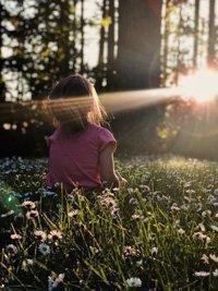 meisje in het gras aan daglicht blootgesteld